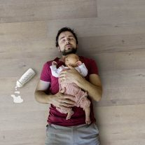 Father holding newborn baby girl, wooden background.